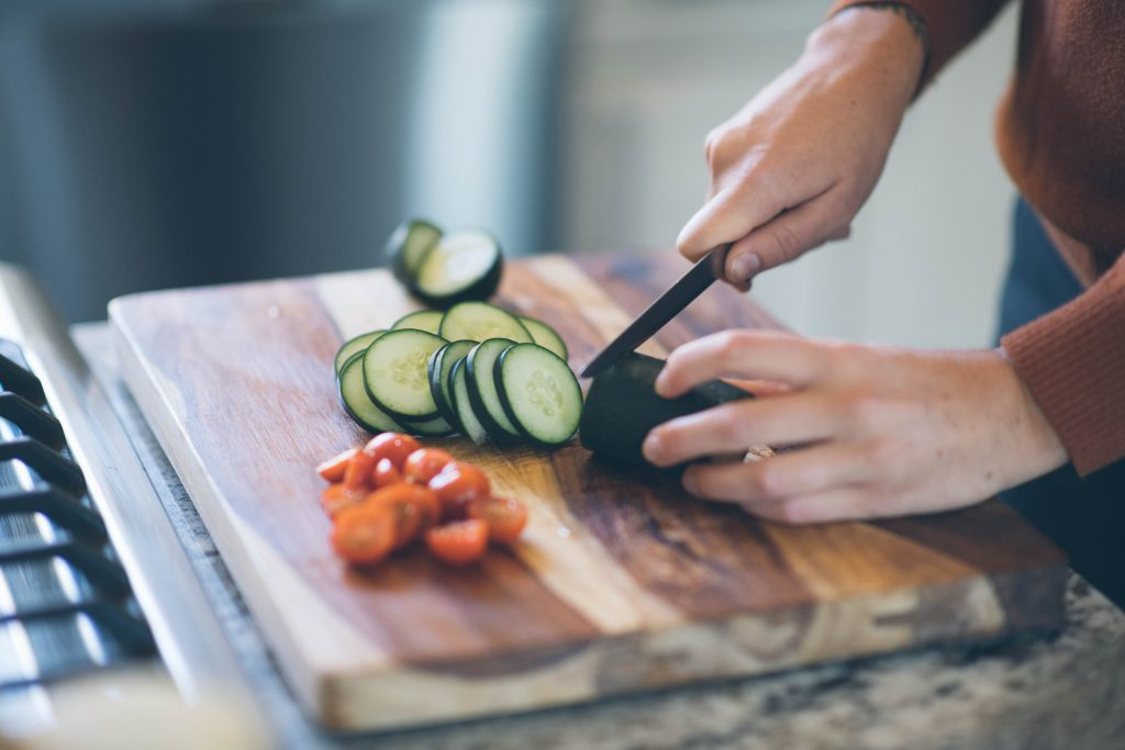 close up shot of cucumber being sliced on a wood cutting board