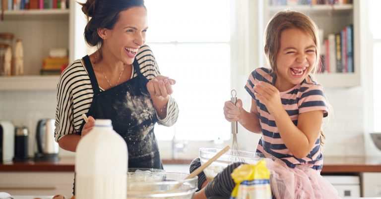 mom and daughter laughing and baking in the kitchen