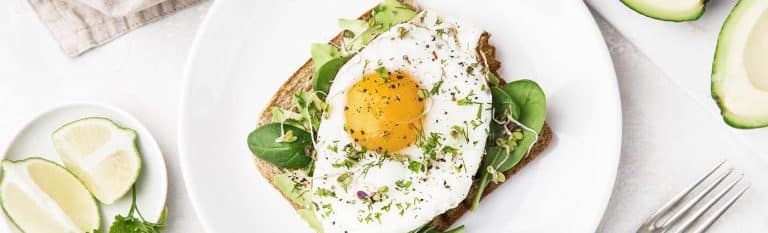 overhead shot of toast with avocado, spinach and fried egg