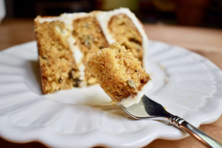a slice of carrot cake with focus on a fork with a bite ready to eat