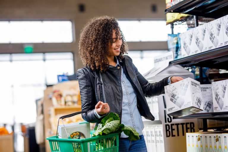 Young girl in grocery store with a shopping basket in one arm and grabbing a box off the shelf