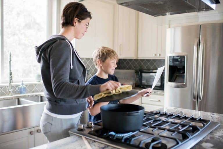 a woman holds open the lid of a pot, while son hold up recipe instructions on a piece of paper