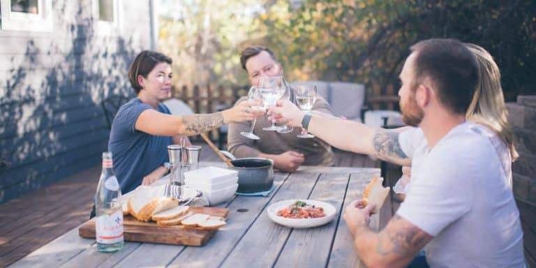 group of four young adults at an outdoor table, clinking glasses over food