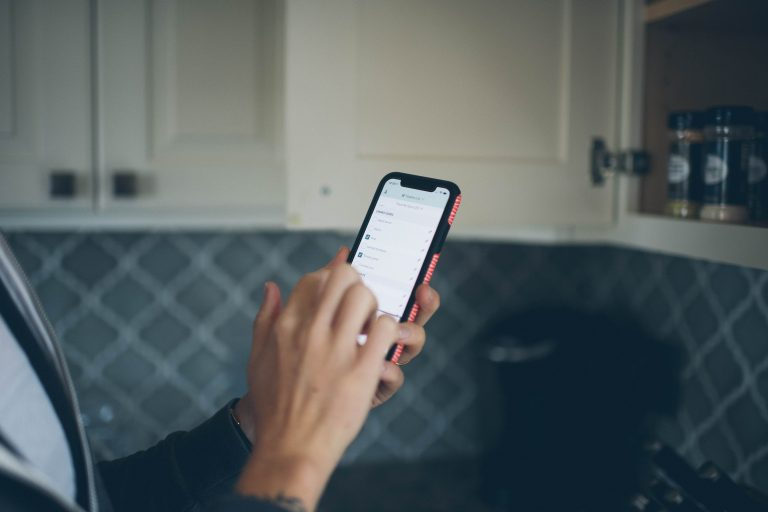 Cropped image of a hand holding a phone in a kitchen with a shopping list on screen