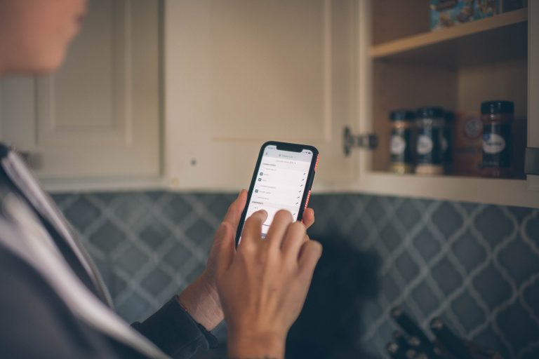 Cropped image of a person holding a phone in the kitchen with a shopping list loaded