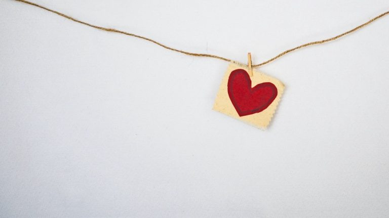 A red paper heart on a string with a white background