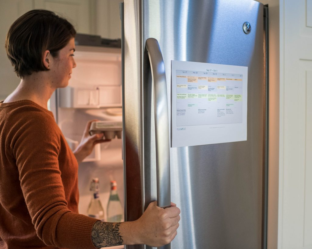 cropped image of a woman looking in a refrigerator