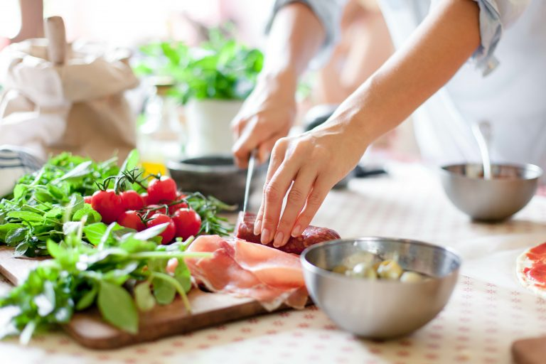 cropped image of woman's hands chopping vegetables and meat on a cutting board