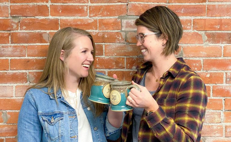 two young women cheersing blue mugs with a brick background