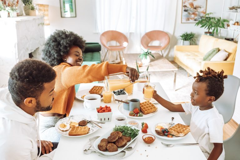 Mom, Dad and child sitting at a table eating breakfast - light colors, white dining room