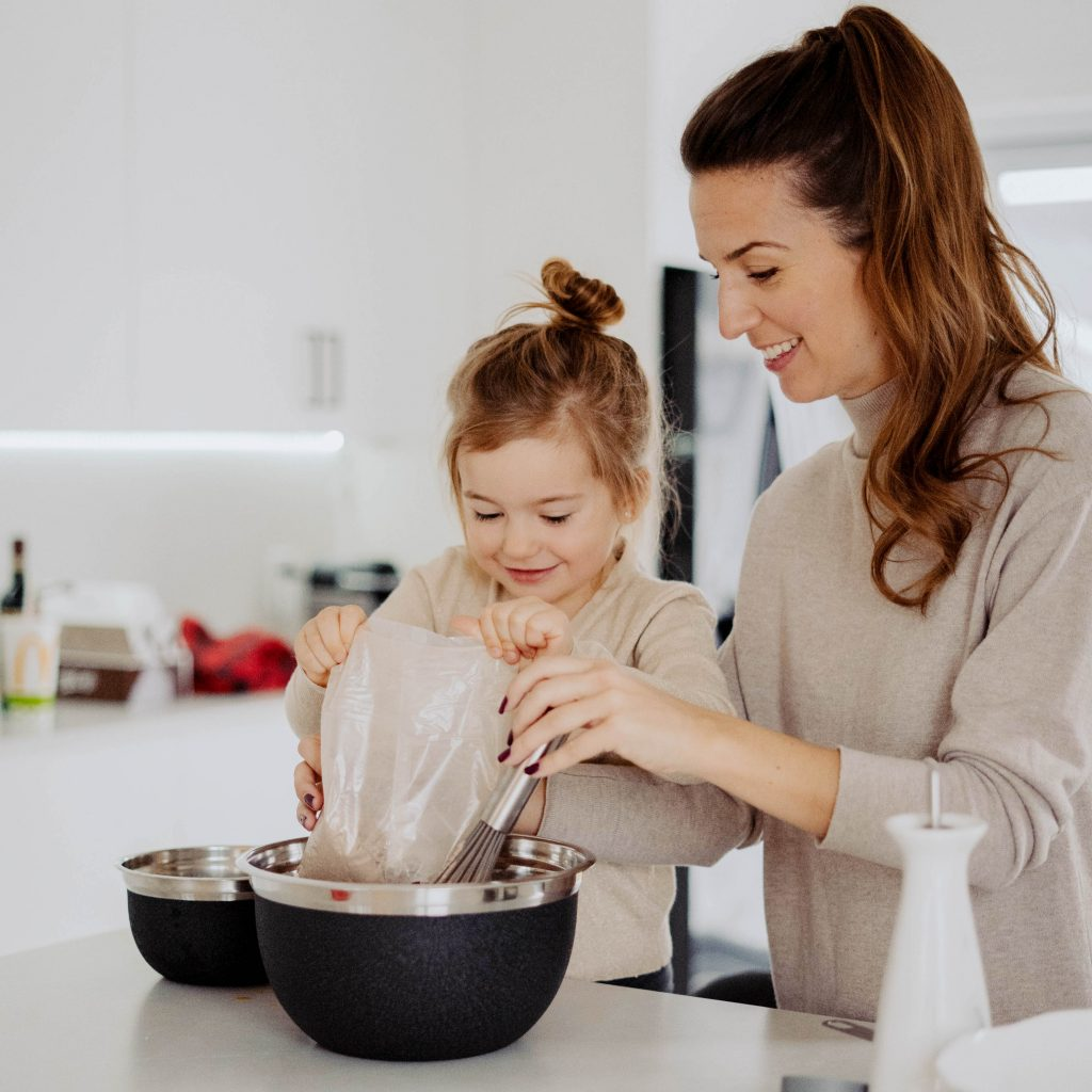 Young mom and daughter making cupcakes in a white kitchen