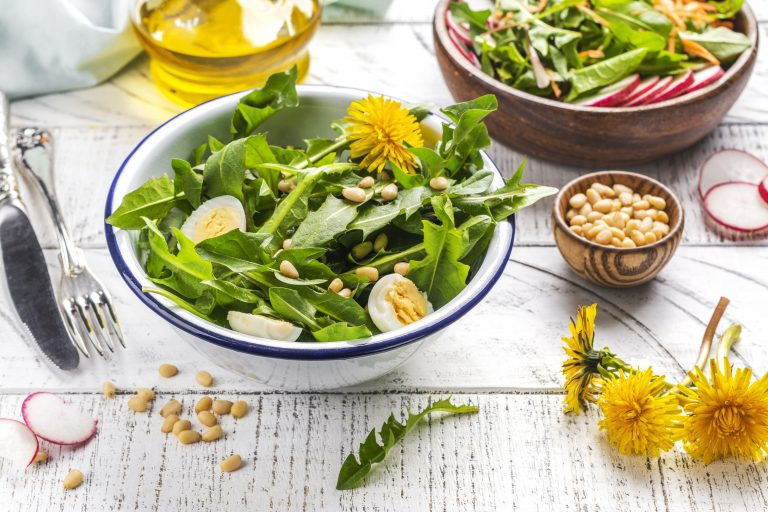 Fresh dandelion salad with nuts, boiled eggs and radish on white background.