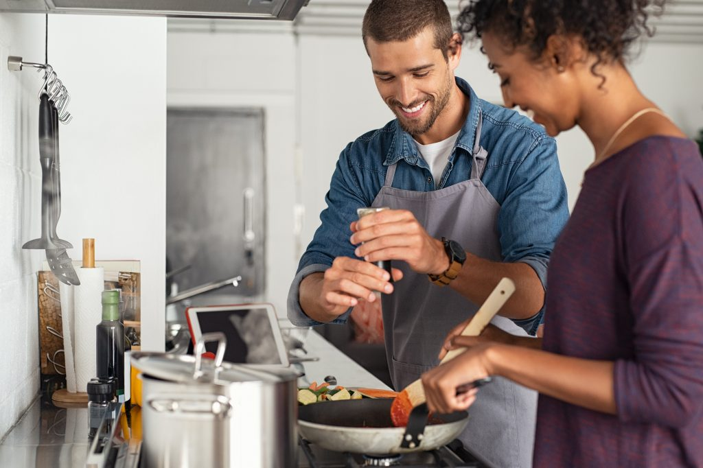 Man adding pepper to tomato sauce, while woman stirs with wooden spoon