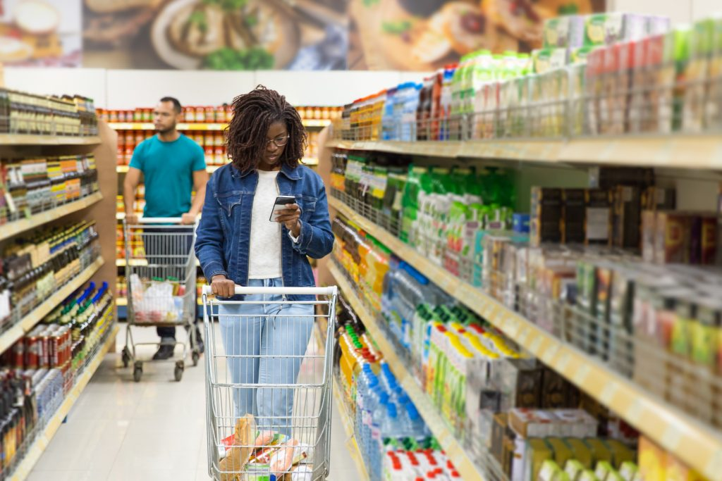 Front view of woman reading shopping list on smartphone. Serious woman with dreadlocks looking at smartphone. Shopping concept