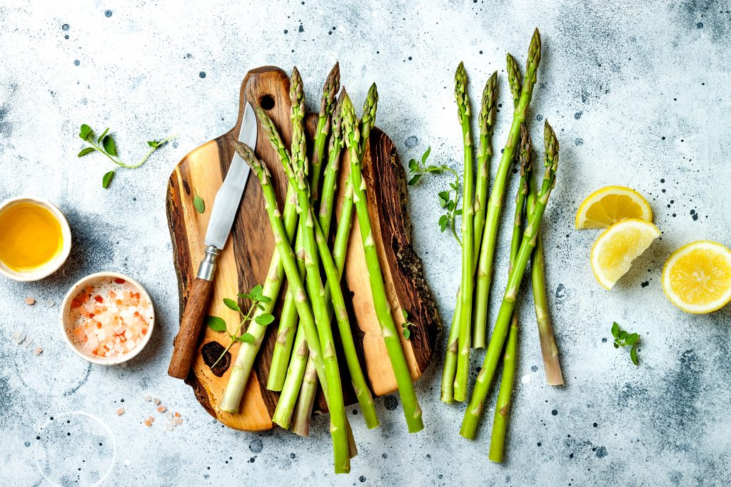 Bunch of fresh green asparagus on wooden board with olive oil, lemon and seasonings.