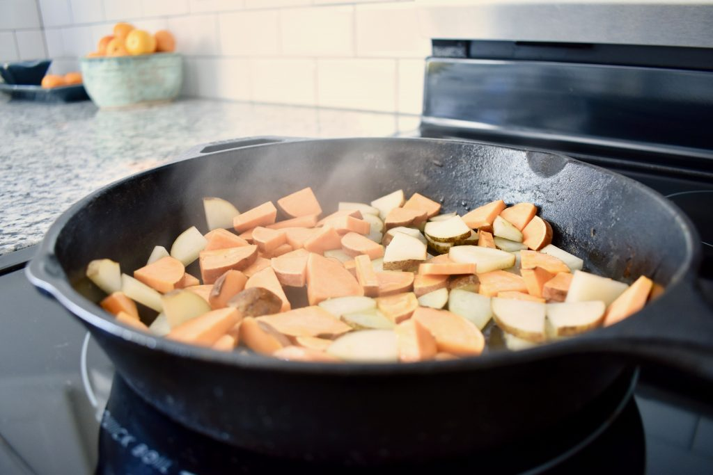 potatoes sauteing in a cast iron pan