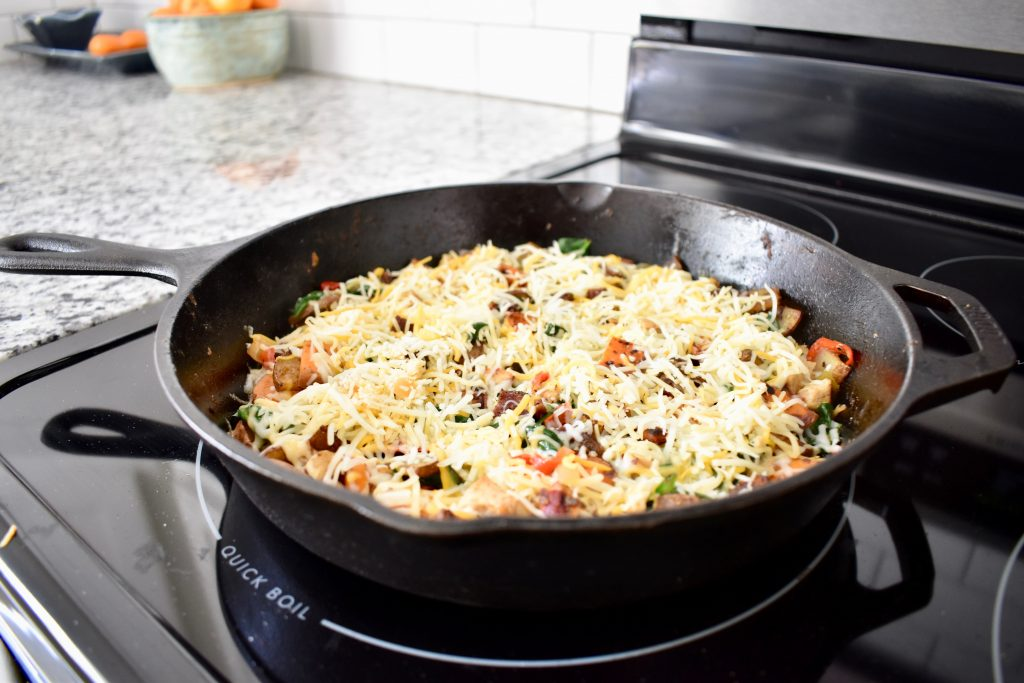 cooked meat and vegetables covered in shredded cheese in a cast iron pan
