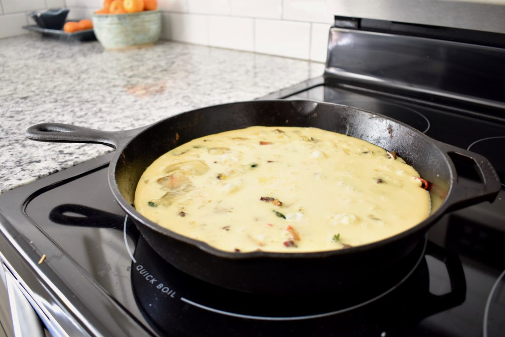 raw frittata before baking in a cast iron pan