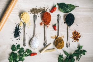 Overhead shot of colorful spices on spoons in a row laying on a table