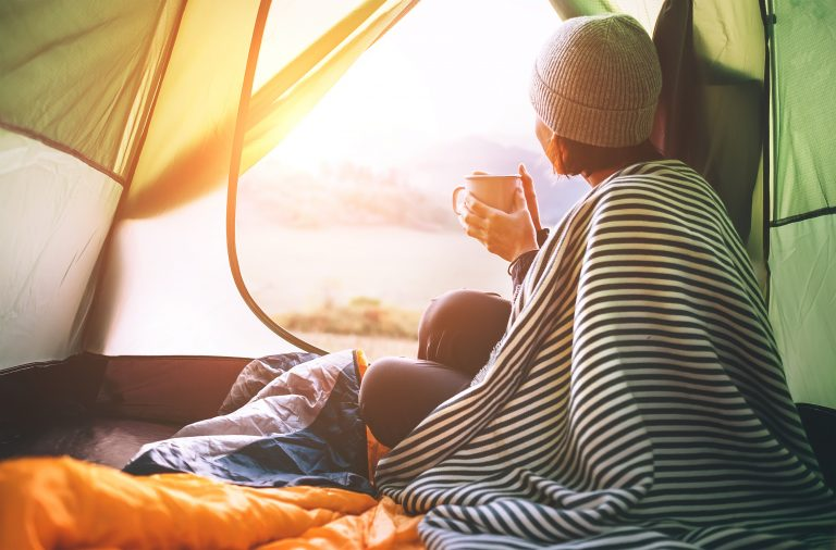 woman looks out the opening of a tent with a blanket on her shoulder and a hot drink in her hands