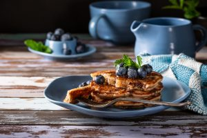 Delicious pancakes with honey and blueberries.