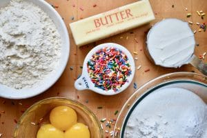overhead shot of flour, butter, eggs and sprinkles. Ingredients needed for cookies