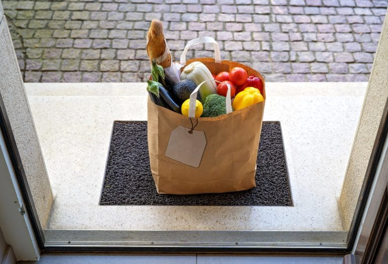 Contactless food delivery service concept. Paper bag with groceries delivered and left outside at entrance door. View from inside through open door. Online shopping. Zero waste package
