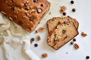 overhead shot of sliced banana bread loaf with chocolate chips scattered on white backround