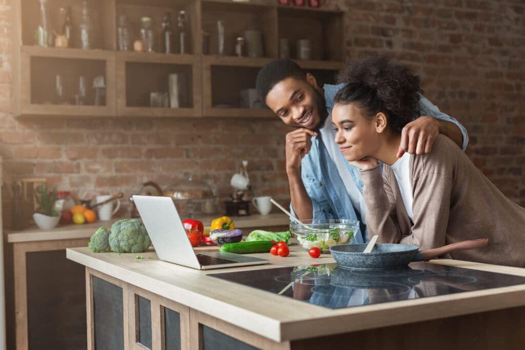 African-american couple cooking dinner with recipe on laptop in loft kitchen