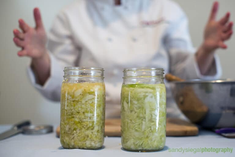 two jars of sauerkraut on a counter in front of a person