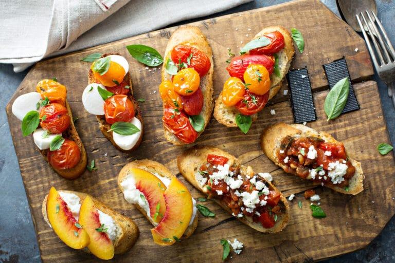 Crostini or bruschetta board with caprese, tomatoes, eggplant caponata and peaches