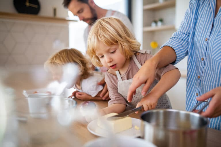 A young family with two small children indoors in kitchen, preparing food.