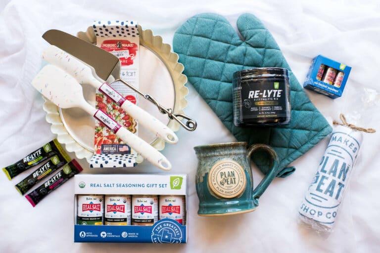 flat lay of giveaway items, including: baking mitt, Redmond Real Salt shakers, spatulas, coffee mug and baking tart