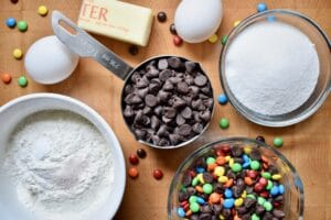 overhead shot of brownie ingredients, chocolate chips, sugar, flour, eggs and buttoner on a brown table
