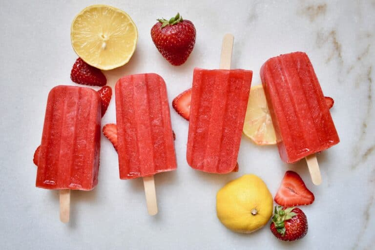 overhead shot of strawberry popsicles with lemons and strawberries around them