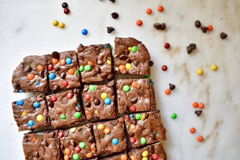 cropped overhead shot of baked brownies, cut into squares with m&ms scattered around