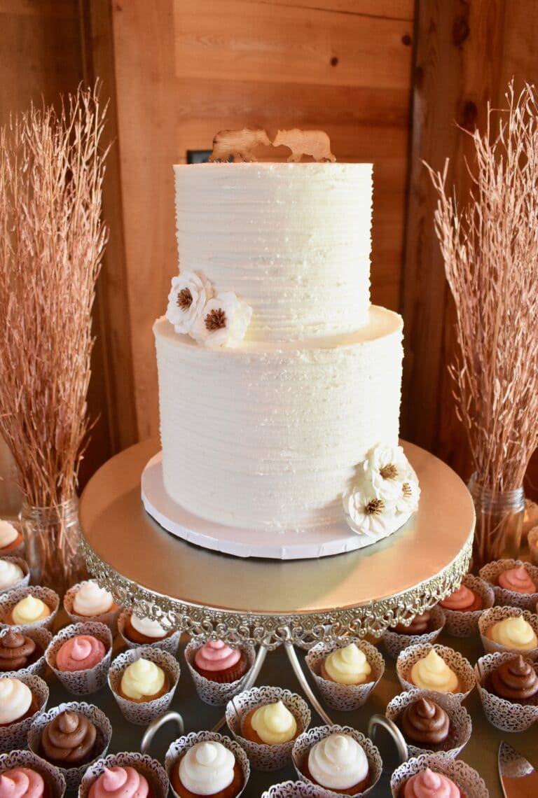 side image of two-tier white wedding cake with cupcakes at the bottom