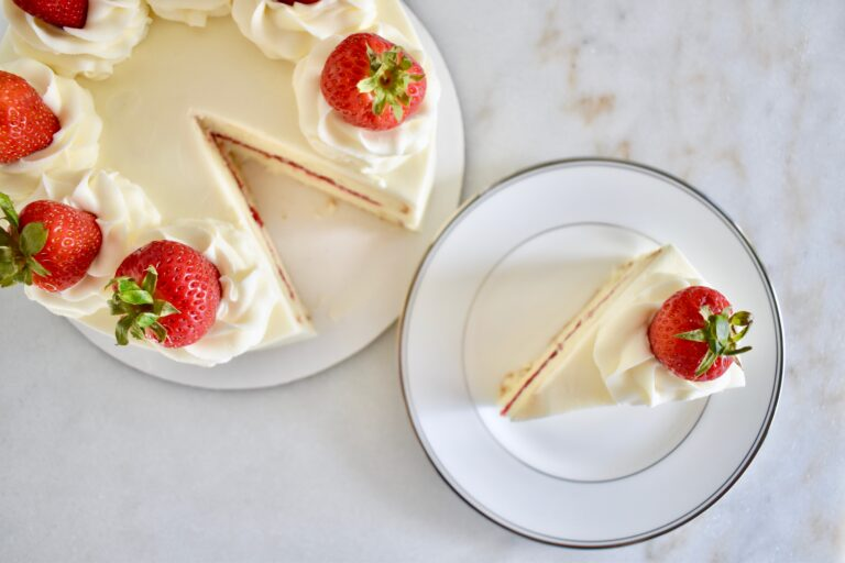 overhead shot of white cake with buttercream and strawberries